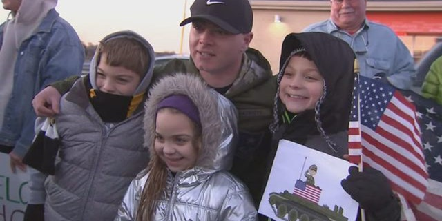 Beau Schlichting posed with young well-wishers at his suprising homecoming party Saturday in Winthrop, Mass. Schlichting returned home after a nine-month deployment in Afghanistan with the U.S. Army.