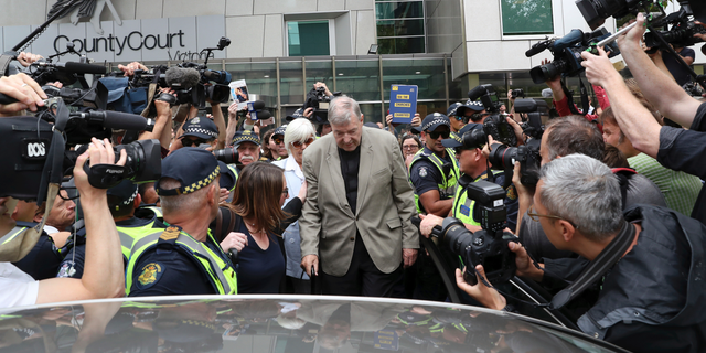 Cardinal George Pell, center, leaves the County Court in Melbourne, Australia, Tuesday, Feb. 26, 2019. The most senior Catholic cleric ever charged with child sex abuse has been convicted of molesting two choirboys moments after celebrating Mass, dealing a new blow to the Catholic hierarchy's credibility after a year of global revelations of abuse and cover-up. (David Crosling/AAP Image via AP)