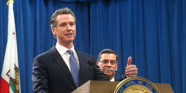California Gov. Gavin Newsom, left, flanked by Attorney General Xavier Becerra, right, answers a question concerning a lawsuit the state will likely file against President Donald Trump over his emergency declaration to fund a wall on the U.S.-Mexico border Friday, Feb. 15, 2019, in Sacramento, Calif. Newsom and Becerra both say there is no emergency at the border and Trump doesn't have the authority to make the declaration. (AP Photo/Rich Pedroncelli)