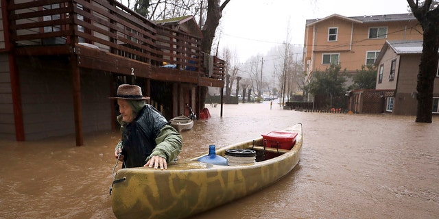 Sycamore Court resident Jesse Hagan evacuates to higher ground in the apartment complex in lower Guerneville, Calif., Tuesday, Feb. 26, 2019.