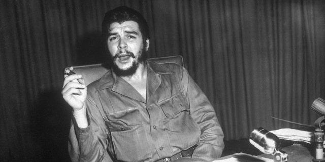 "1960- Portrait of Ernesto ""Che"" Guevara, Cuban revolutionary leader, sitting at a desk."
