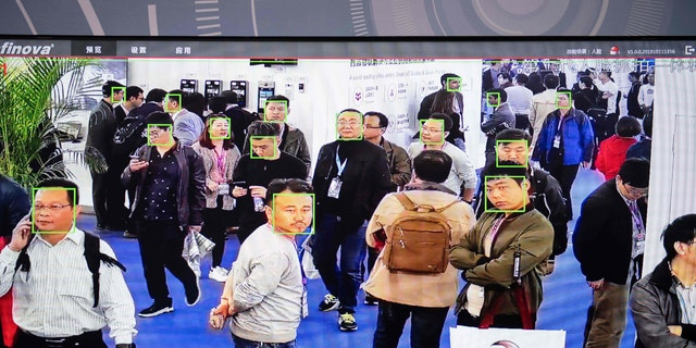 A screen shows visitors being filmed by AI (Artificial Intelligence) security cameras with facial recognition technology at the 14th China International Exhibition on Public Safety and Security in Beijing.