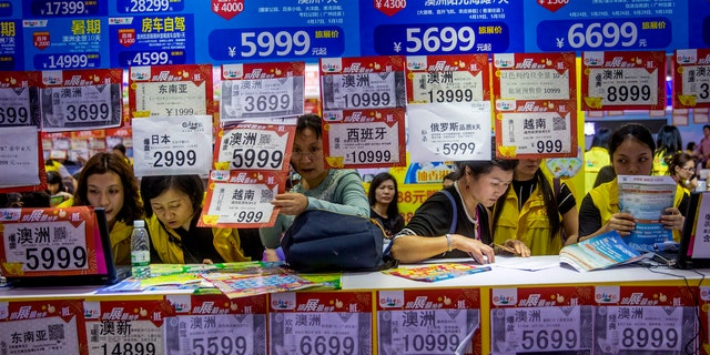 """In this March 3, 2018, photo, people check on travel packages offered by travel agencies during the Guangzhou International Travel Fair in Guangzhou in south China's Guangdong province. Travelers in China were blocked from buying plane tickets 17.5 million times last year as a penalty for failing to pay fines or other offenses. The Chinese government reported this week on penalties imposed under a controversial """"social credit"""" system the ruling Communist Party says will improve public behavior. (Chinatopix via AP)"""