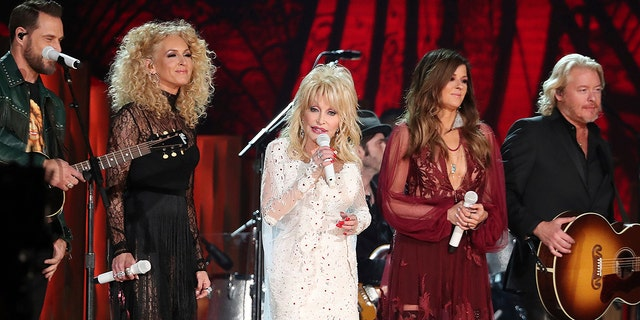 """Dolly Parton, center, Jimi Westbrook, from left, Kimberly Schlapman, Karen Fairchild, and Philip Sweet, of Little Big Town, perform """"Red Shoes"""" at the 61st annual Grammy Awards on Sunday, Feb. 10, 2019, in Los Angeles. (Photo by Matt Sayles/Invision/AP)"""