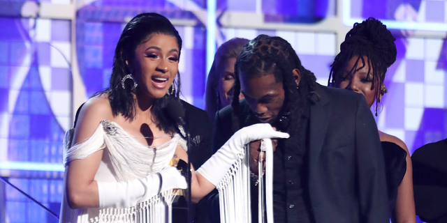 """Cardi B, left, accepts the award for best rap album for """"Invasion of Privacy"""" as Offset kisses her hand at the 61st annual Grammy Awards."""