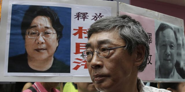 """In this June 18, 2016, file photo, freed Hong Kong bookseller Lam Wing-kee stands next to a placard with picture of missing bookseller Gui Minhai, in front of his book store in Hong Kong as the protesters are marching to the Chinese central government's liaison office. Sweden has condemned China's """"brutal"""" detention of a Swedish citizen who sold politically sensitive books and whose seizure while he traveled with diplomats stunned Western governments."""