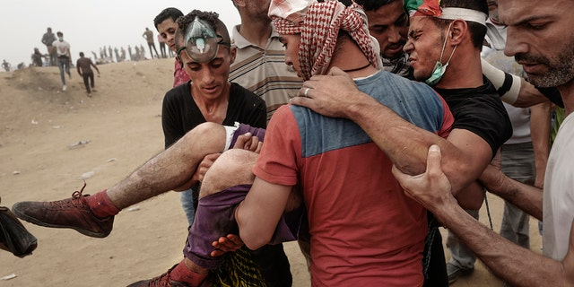 A wounded Palestinian protester is taken away during clashes with Israeli forces on May 4, 2018 in Khan Yunis, Gaza.