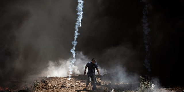 A tear gas canister falls near a Palestinian at the border fence with Israel as mass demonstrations continue on May 14, 2018 in Gaza City, Gaza.