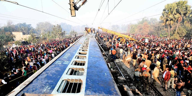 Rescue workers look for survivors as locals stand around the derailed coaches of a train, 30 kilometers (20 miles) north of Patna, the Bihar state capital of India, Sunday, Feb. 3, 2019. (AP Photo)