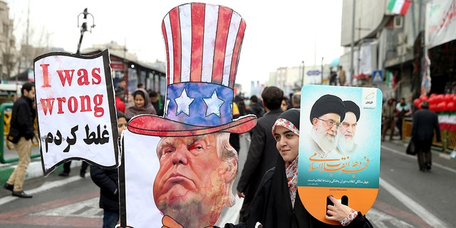 An Iranian woman holds an effigy of US president Donald Trump, during a rally marking the 40th anniversary of the 1979 Islamic Revolution, in Tehran, Iran, Monday, Feb. 11, 2019.