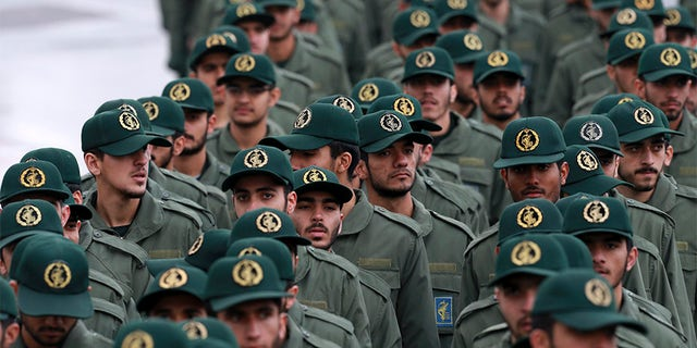 """Iranian Revolutionary Guard members arrive for a ceremony celebrating the 40th anniversary of the Islamic Revolution in Tehran, Iran, on Monday. Four Iranians dubbed the """"Cyber Conspirators"""" by the Justice Department, are accused of working on behalf of the military unit to 'deploy malware that would provide them covert access to the targets' computers and networks.'"""