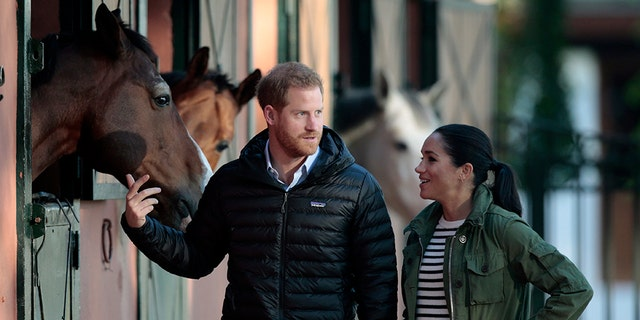 Britain's Prince Harry and Meghan, Duchess of Sussex, walk together during a visit to the Moroccan Royal Equestrian Sports Complex in Rabat, Morocco, Monday Feb. 25, 2019. The royal couple, who are expecting their first child in Spring 2019, are visiting the prestigious equestrian club to see the use of horses in therapy for children with disabilities.(AP Photo/Mosa'ab Elshamy)