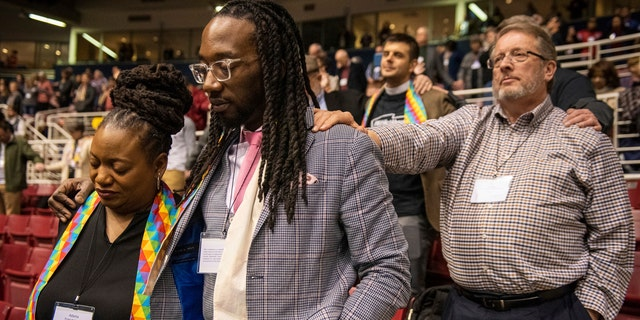 Adama Brown-Hathasway, left, The Rev. Dr. Jay Williams, both from Boston, and Ric Holladay of Kentucky join in prayer during the 2019 Special Session of the General Conference of The United Methodist Church in St. Louis