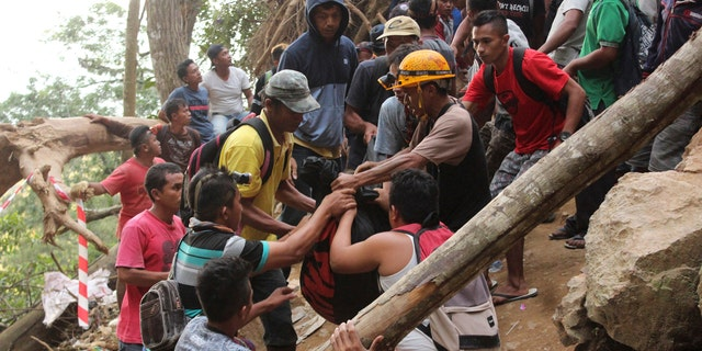 Rescuers carry the body of a victim of a collapsed mine in Bolaang Mongondow, North Sulawesi, Indonesia, Wednesday, Feb. 27, 2019.