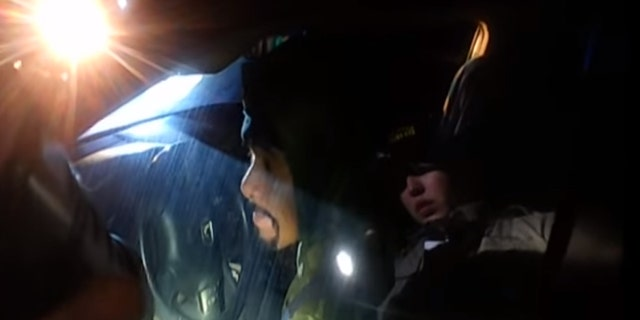 Napa County Sheriff's Deputy Riley Jarecki can be seen in a refection on the window of a car, asking Javier Hernandez Morales to roll down the window.