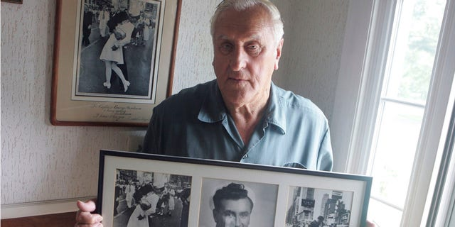 In this July 2, 2009, photo George Mendonsa poses for a photo in Middletown, R.I., holding a copy of the famous Alfred Eisenstadt photo of Mendonsa kissing a woman in a nurse's uniform in Times Square on Aug. 14, 1945, while celebrating the end of World War II, left. Mendonsa died Sunday, Feb. 17, 2019, he was 95.