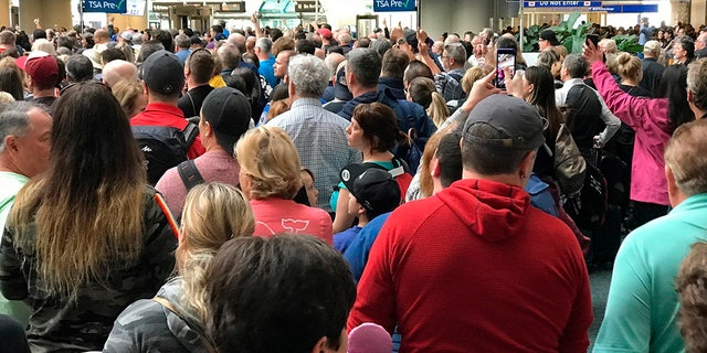 People wait to get through security at the Orlando International Airport following a security incident on Saturday, after flights were grounded following an apparent suicide. (Jonathan Hayward/The Canadian Press via AP)