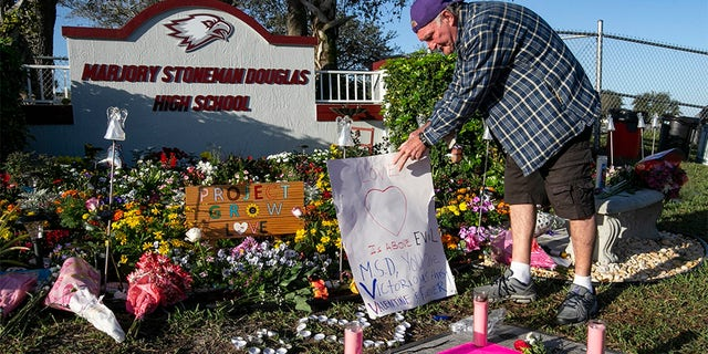 Jack Jozefs places a sign at a memorial outside Marjory Stoneman Douglas High School, Thursday, on the one-year anniversary of the deadly shooting at the school that killed 17 people, in Parkland, Florida.