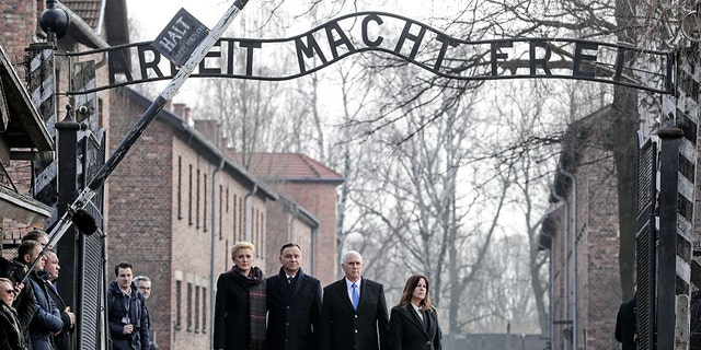 """United States Vice President Mike Pence and his wife Karen Pence, right, stand with Poland's President Andrzej Duda and his wife Agata Kornhauser-Duda, left, under the gate during their visit at the Nazi concentration camp Auschwitz-Birkenau in Oswiecim, Poland, Friday, Feb. 15, 2019. They stand under the infamous """"Arbeit Macht Frei"""" sign"""