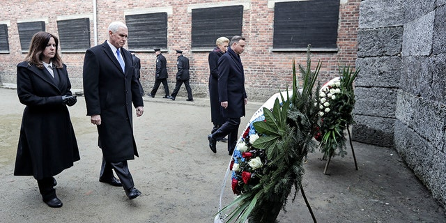 Vice President Mike Pence and his wife Karen Pence, left, walk with Poland's President Andrzej Duda and his wife Agata Kornhauser-Duda, right, to wreaths at a death wall during their visit at the Nazi concentration camp Auschwitz-Birkenau in Oswiecim, Poland, Friday. (AP Photo/Michael Sohn)