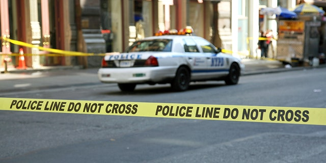 Police tape hangs across a street in front of a building, New York City, New York, USA.