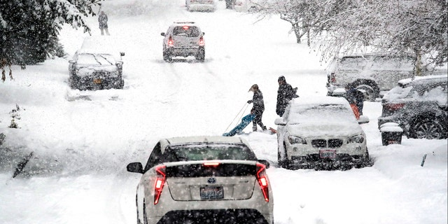 A sledder moves aside as traffic heads downhill in heavy snow falling Monday, Feb. 11, 2019, in Seattle.