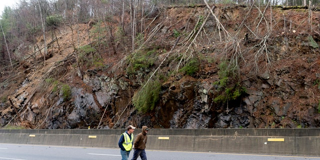 Workers pass by the scene of a mudslide on I-40 eastbound in Clyde, N.C., near the Tennessee and North Carolina border on Saturday, Feb. 23, 2019.