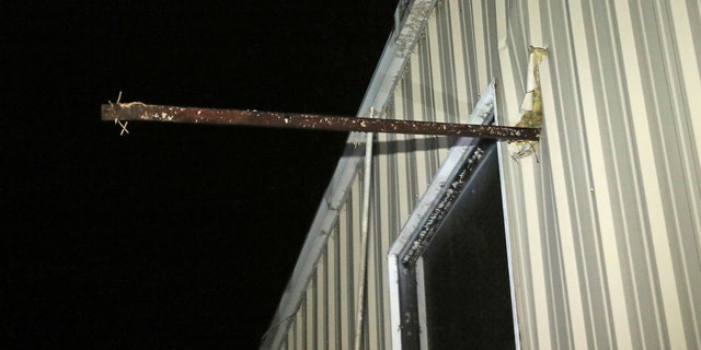 A metal pipe sticks through the exterior wall of Fast Dog Printing Co. on Conway Drive in Columbus, Miss., after a tornado struck the area Saturday, Feb. 23, 2019.