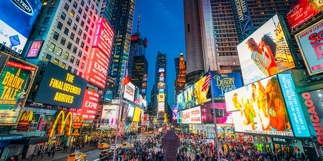 Times Square covered with illuminated billboards as tourists flock the streets.