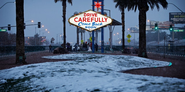 """Snow accumulates on a median along the Las Vegas Strip at the """"Welcome to Fabulous Las Vegas"""" sign, Thursday, Feb. 21, 2019, in Las Vegas."""
