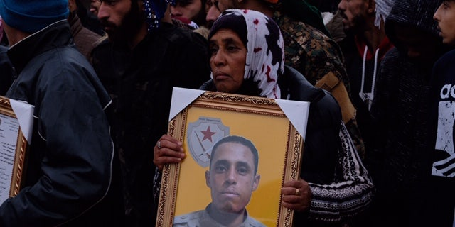 A grieving mother holds a portrait of her son who was killed fighting ISIS in Deir-ez-Zor in January 2019.