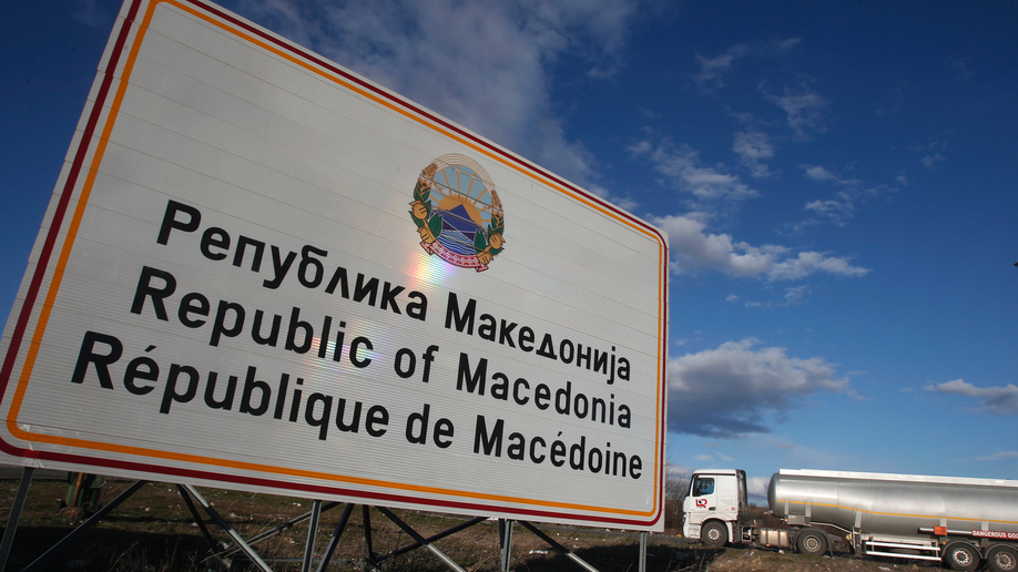 Workers in North Macedonia replace signs to reflect new name