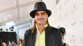 Patriotically attired, Kid Rock hits links with Trump