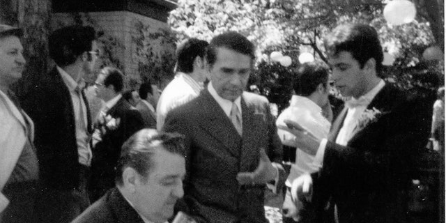 """(L to R foreground) On the wedding set of """"The Godfather,"""" one of Joe Columbo's enforcers (seated), Richard Conte and Gianni Russo (standing.)"""