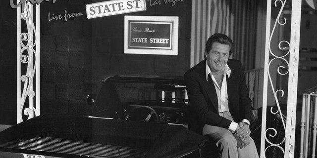 """Gianni Russo, seated on the black Ferrari parked in front his State Street Club, poses for the album cover art, """"Live from State Street."""""""