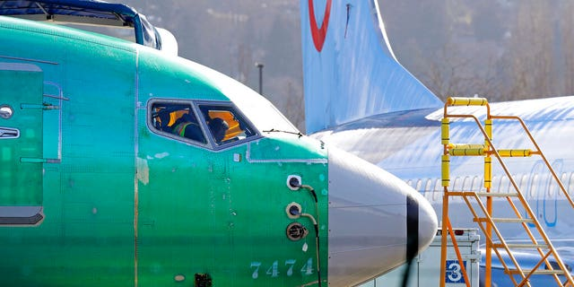 In this March 13, 2019, file photo people work in the flight deck of a Boeing 737 MAX 8 airplane being built for TUI Group parked next to another MAX 8 also designated for TUI at Boeing Co.'s Renton Assembly Plant in Renton, Wash.