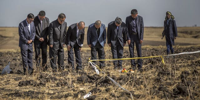 Officials from the Aviation Industry Corporation of China (AVIC) pray next to an offering of fruit, bread rolls, and a plastic container of Ethiopian Injera, a fermented sourdough flatbread, placed next to incense sticks, at the scene where the Ethiopian Airlines Boeing 737 Max 8 crashed shortly after takeoff on Sunday killing all 157 on board, near Bishoftu, or Debre Zeit, south of Addis Ababa, in Ethiopia.