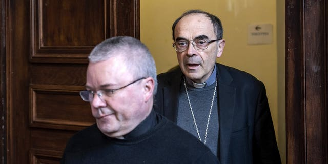 French Cardinal Philippe Barbarin, right, arrives for a press conference in Lyon, central France, Thursday, March 7, 2019. Barbarin offers his resignation to the Pope after a court on Thursday found him guilty of failing to report to authorities allegations of sexual abuse of minors by a priest.