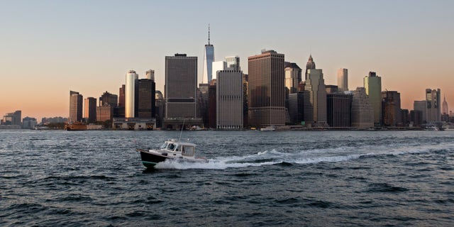 FILE - In this Oct. 19, 2017 file photo, a boat crosses New York Harbor in front of the Manhattan skyline. Mayor Bill de Blasio is announcing a plan to protect lower Manhattan from rising sea levels by surrounding it with earthen berms and extending its shoreline by as much as 500 feet. (AP Photo/Mark Lennihan, File)