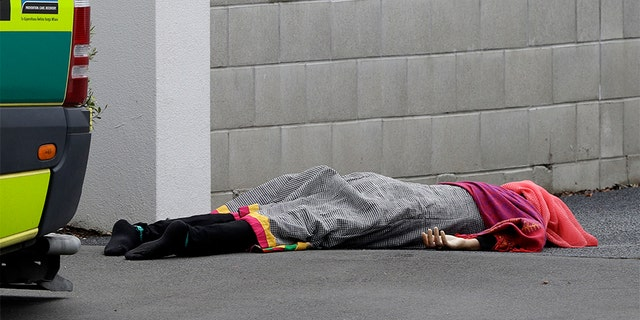 A body lies on the footpath outside a mosque in central Christchurch, New Zealand, on Friday.
