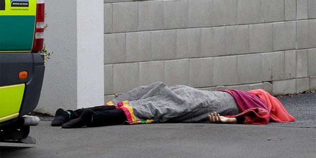 शुक्रवार को न्यूजीलैंड के सेंट्रल क्राइस्टचर्च में एक मस्जिद के सामने एक शव फुटपाथ पर टिका हुआ है। (एपी)