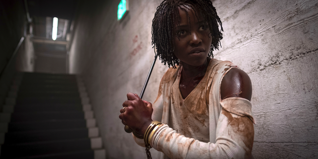 This design expelled by Universal Pictures shows Lupita Nyong'o in a stage from Us, written, constructed and destined by Jordan Peele.