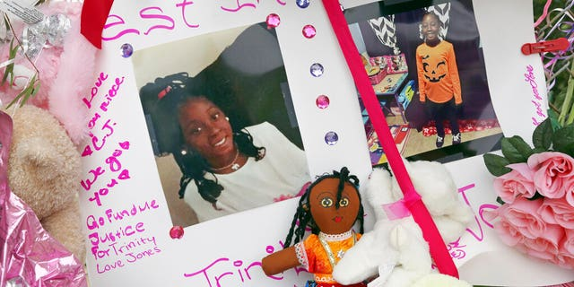 Photos adorn a large memorial to Trinity Love Jones, the 9-year-old girl whose body was found in a duffel bag along a suburban Los Angeles equestrian trail.