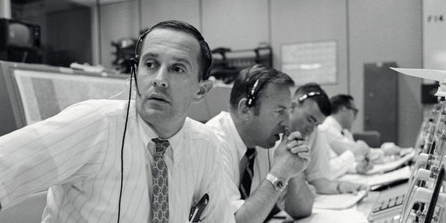 File print - Spacecraft communicators are graphic as they keep in hit with a Apollo 11 astronauts during their lunar alighting goal on Jul 20, 1969. From left to right are astronauts Charles M. Duke Jr., James A. Lovell Jr. and Fred W. Haise Jr.