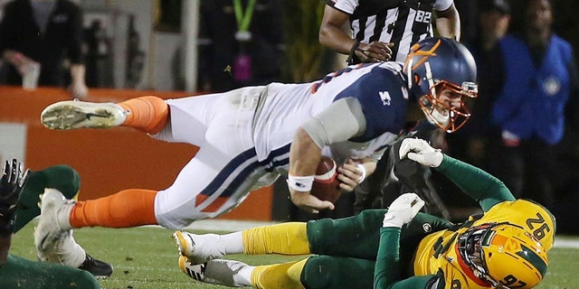 Orlando Apollos quarterback Garrett Gilbert dives over Arizona Hotshots defensive end Rykeem Yates (92) during an Alliance of American Football game in Orlando, Fla., on March 16. (Associated Press)