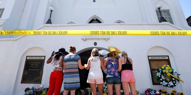 In this June 18, 2015, file photo, a group of women pray together at a makeshift memorial on the sidewalk in front of the Emanuel AME Church, in Charleston, S.C. Dylann Roof, shot a killed nine people while they were in a bible study at the church. A shooting at a Tennessee church on Sunday, Sept. 24, 2017, has demonstrated again that deadly violence at U.S. houses of worship is not rare. (AP Photo/Stephen B. Morton, File)