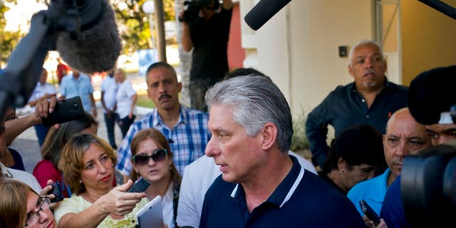 Cuba's President Miguel Diaz-Canel talks to the press after voting in a referendum to approve or reject the new constitution in Havana, Cuba, Sunday, Feb. 24, 2019. The constitutional reforms maintain Cuba's single-party political system and centrally planned economy while recognizing private property and small businesses, which have been part of the island's economy without formal legal status for more than a decade. (AP Photo/Ramon Espinosa)