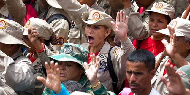 """Members of the Bolivarian Militia raise their hands swearing allegiance to the fatherland during an """"anti-intervention"""" march coinciding with the anniversary of the deadly 1989 social uprising against neoliberal measures known as the Caracazo, in Caracas, Venezuela, Wednesday, Feb. 27, 2019. (AP Photo/Ariana Cubillos)"""