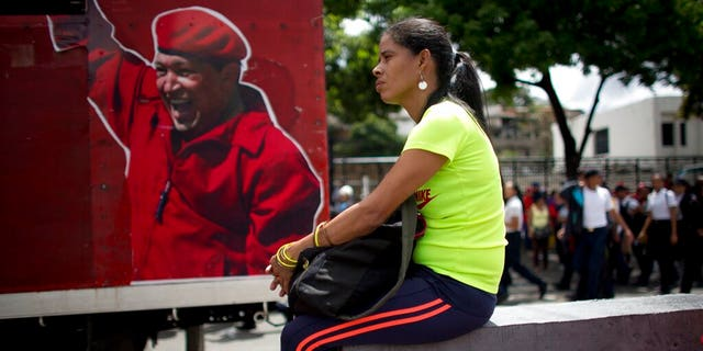 """A supporter of Venezuela's President Nicolas Maduro sits next to an image depicting the late president Hugo Chavez during an """"anti-intervention"""" march coinciding with the anniversary of the deadly 1989 social uprising against neoliberal measures known as the Caracazo, in Caracas, Venezuela, Wednesday, Feb. 27, 2019. (AP Photo/Ariana Cubillos)"""
