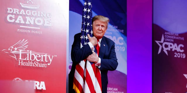 President Donald Trump hugs the American flag as he arrives to speak at Conservative Political Action Conference.